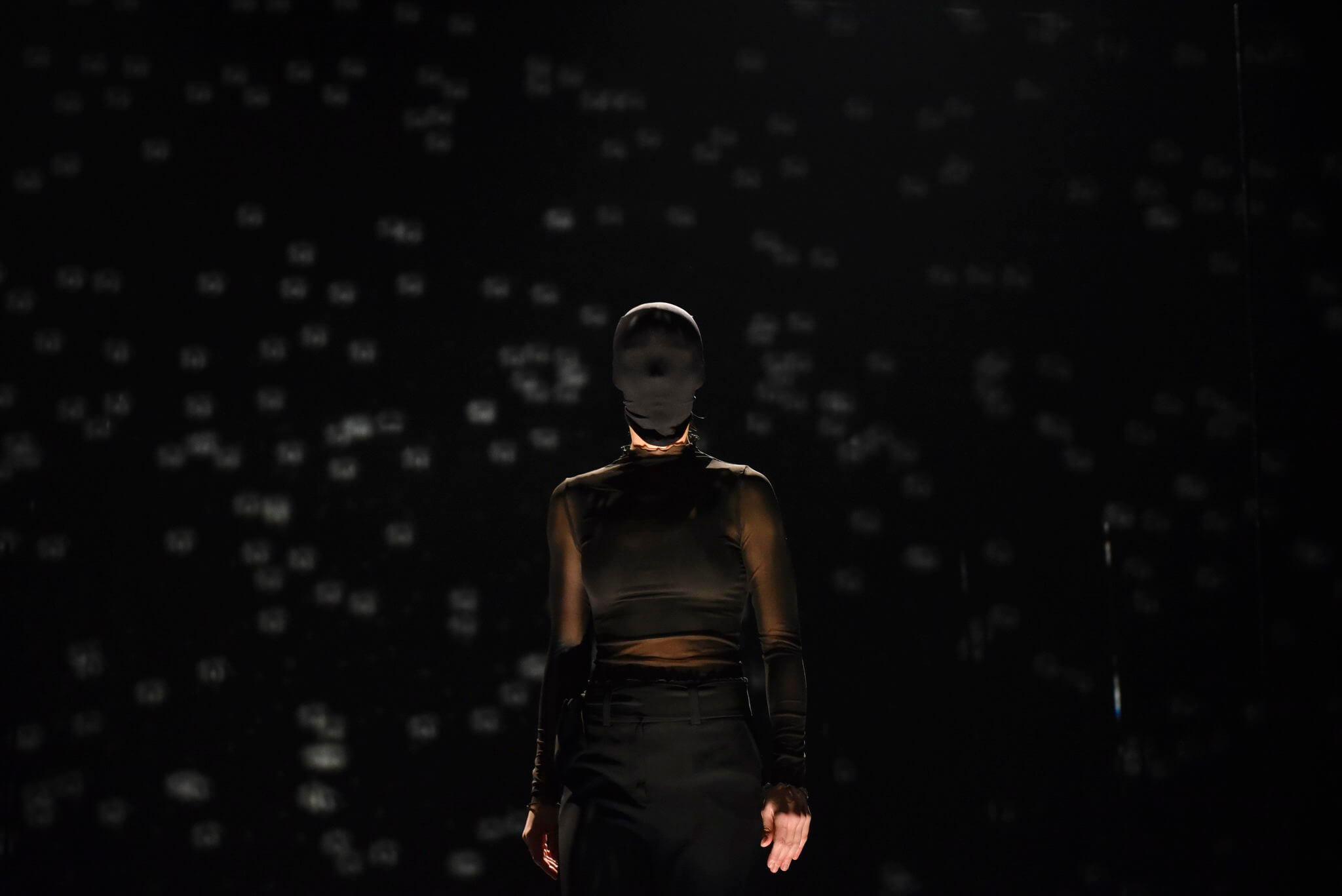 zena sa maskom preko glave pred publikom