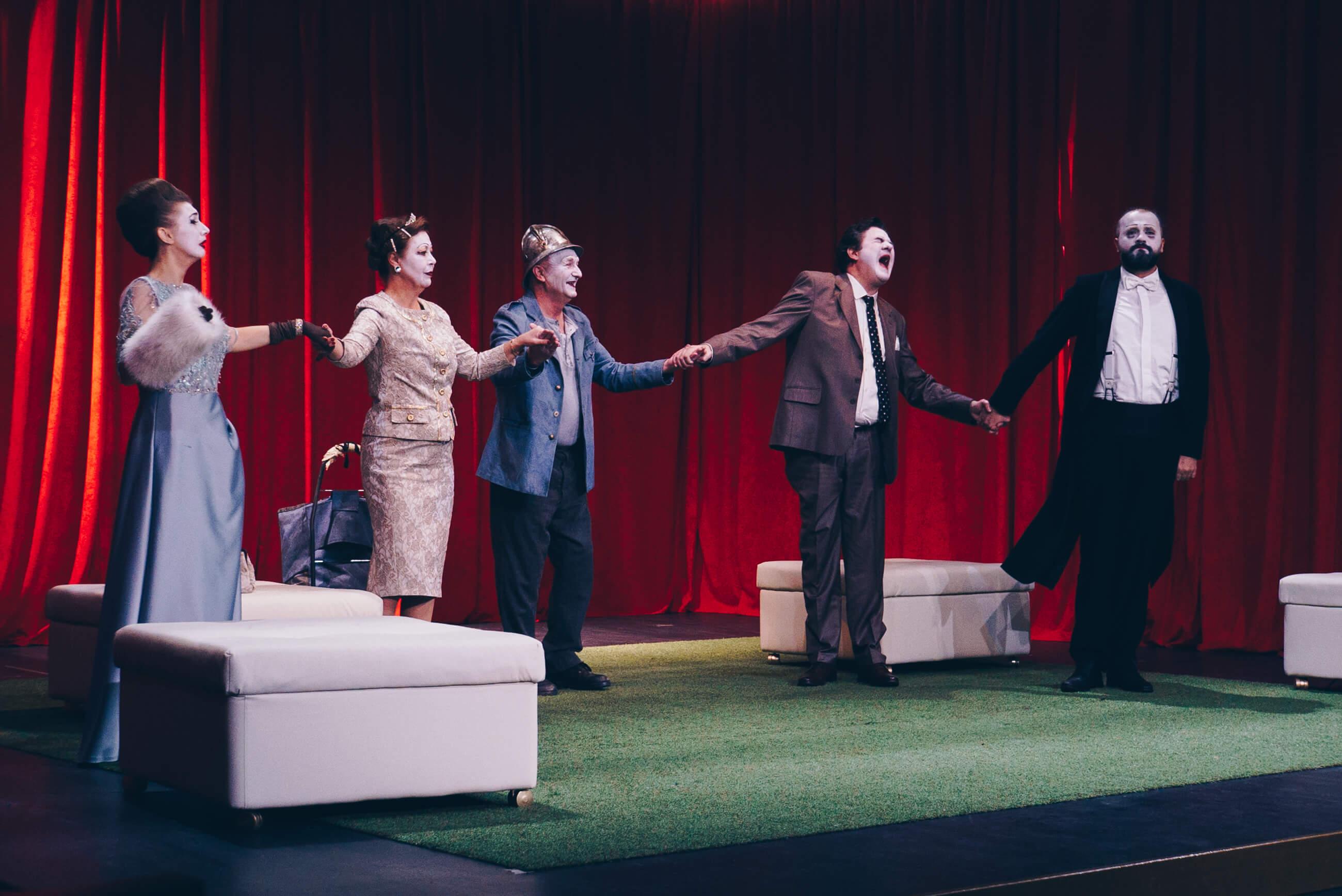 glumci pevaju i drze se za ruke